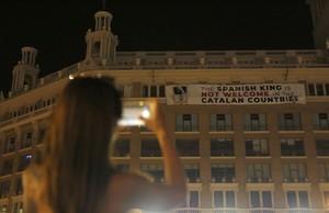 Una viandante fotografía desde la Plaza de Catalunya de Barcelona la plancarta colgada la noche del pasado 16 de agosto para protestar por la presencia del Rey Felipe VI en Catalunya.
