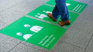 Adhesivos en el suelo en el aeropuerto de Frankfurt que recuerdan a sus usuarios la necesidad de seguir las normas de seguridad.