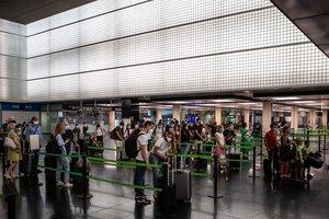 GRAFCAT127. BARCELONA, 24/07/2020.- Varios pasajeros en los mostradores de facturación de la T2 del Aeropuerto de El Prat que se ha puesto nuevamente en servicio este viernes para adaptarse a la situación operativa, facilitar la distancia de seguridad y evitar posibles aglomeraciones en las instalaciones. EFE/Enric Fontcuberta