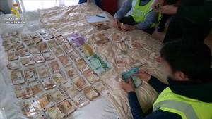 Agentes de la Guardia Civil cuentan parte de los 470.000 euros decomisados.