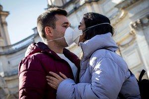 -FOTODELDÍA- EPA044. ROMA (ITALIA), 04/03/2020.- Una pareja se besa con máscaras faciales sanitarias, este miércoles en Roma (Italia), país en el que el coronavirus se sigue expandiendo y ya hay 107 fallecidos de un total de 3.089 contagiados, mientras 276 personas ya se han curado. EFE/ Massimo Percossi
