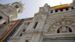 La bandera arcoíris del colectivo LGTBI, instalada en la fachada del Ayuntamiento de Madrid junto a una bandera de España.