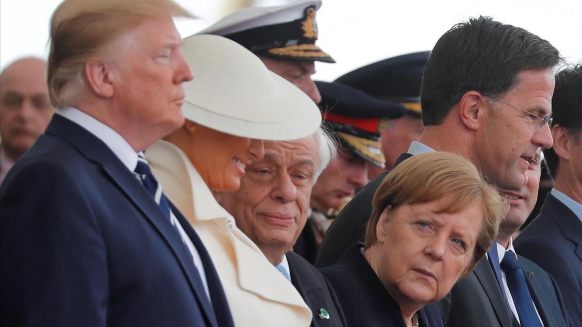 La cancillera alemana, Angela Merkel, mira al presidente de EEUU, Donald Trump, durante los actos de conmemoración del desembarco de Normandía.