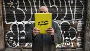 Carlitos González, presidente de la asociación 1010 Ways To Buy Without Money, posa tras un libro que les hicieron los alumnos de Publicidad de la UAB: El libro que necesitas.
