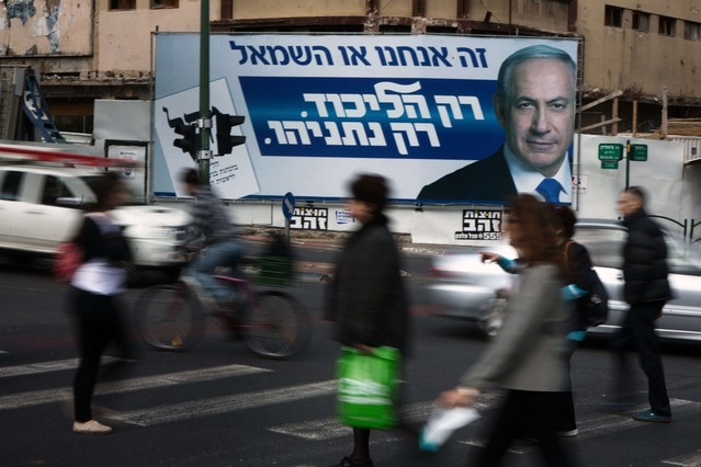 Un cartel propagandístico de Binyamin Netanyahu observa pasar a los ciudadanos israelís.