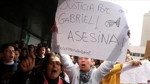 Un centenar de personas gritan pidiendo justicia al paso del furgon policial en Almería, ayer.