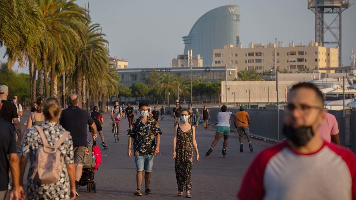 Paseantes con mascarilla por el barrio de la Barceloneta.