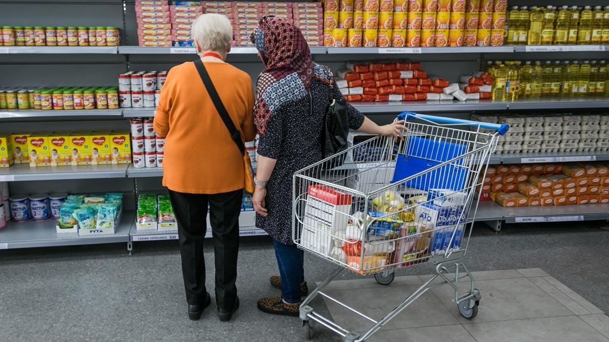 Dos personas observan las estanterías de un economato para familias sin recursos.