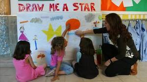 Una maestra de infantil ayuda a sus alumnos a terminar un póster en inglés en un colegio de Barcelona.