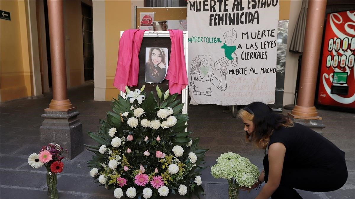 Una mujer coloca flores el miércoles frente a la fotografía de Ingrid Escamilla, una joven de 25 años, víctimade un feminicidio en Puebla.