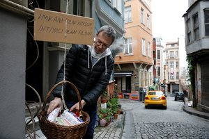 Jeffrey Tucker adds items to a basket he lowered from his window as a sign of social solidarity with poor and homeless people in need amid the coronavirus disease (COVID-19) outbreak in Istanbul, Turkey April 3, 2020. Cardboard reads, Those who have the means, add. Those who need, take REUTERS/Umit Bektas