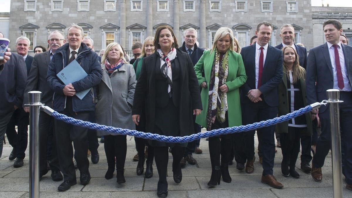 La líder del Sinn Féin, Mary Lou McDonald, posa con los nuevos diputados del partido en el exterior del Parlamento irlandés, este jueves.