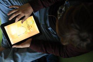 Un niño juega con una tableta digital.