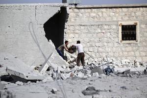 Civiles sacan sus pertenencias de su vivienda bombardeada en una localidad de los alrededores de Alepo.