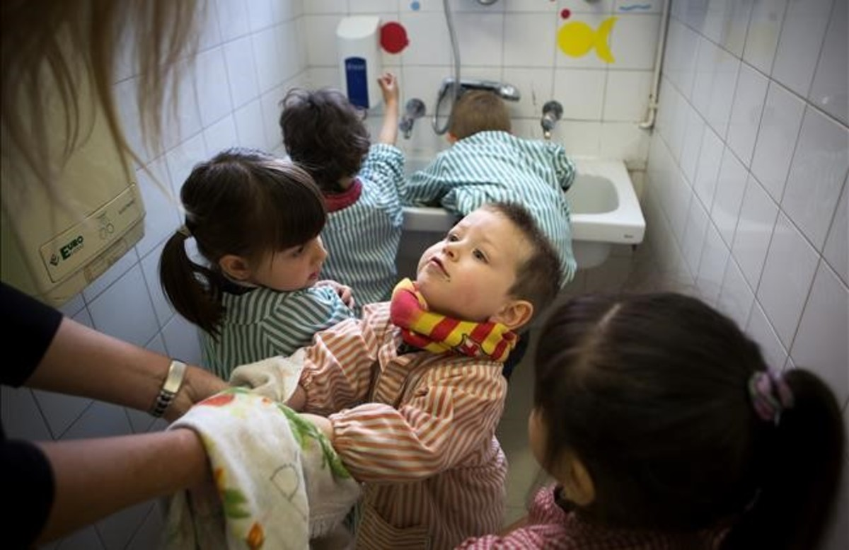 Una profesora ayuda a secarse las manos a sus alumnos de educación infantil antes de ir a comer.