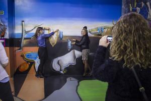 Unas visitantes se fotografían junto a una reproducción de La persistencia de la memoria, de Dalí.