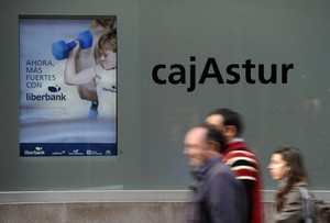 People walk past the Cajastur headquarters, part of Liberbank, in Oviedo, December 20, 2012. Spain's Liberbank on Thursday said it planned a stock listing in the first half of 2013 as part of its recapitalisation plan. The announcement came after the European Commission approved the second phase of Spain's banking sector overhaul. Liberbank will receive a temporary aid of 124 million euros in contingent convertible bonds, also know as Cocos. REUTERS/Eloy Alonso (SPAIN - Tags: BUSINESS)