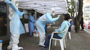 Un sanitario realiza un prueba de covid-19 a una mujer en un hospital de Seúl, este viernes.