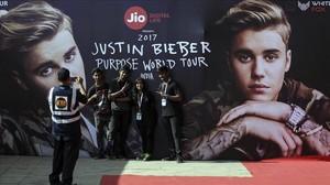 Varios jovenes indios se toman una fotografia con un cartel que publicita la gira mundial del cantante canadiense Justin Bieber antes de su concierto en el estadio Dnyandeo Yashwantrao Patil en Bombay (India).