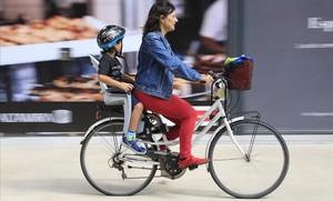 Una madre con su hijo en bicibleta por el barrio de Poblenou.