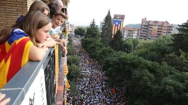 Unos vecinos siguen la manifestación desdel el balcón de un piso, en Berga.