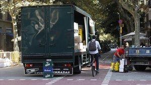 Un camión descarga mercancías en la esquina de las calles Enric Granados y Consell de Cent.