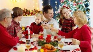 Una familia celebra la Navidad alrededor de la mesa.