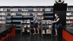 Personal de la biblioteca de la Sagrada Família ordena los libros que pasarán a una cuarentena tras su devolución.