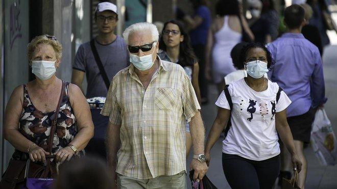 Vecinos del barrio de Sants pasean por la calle con mascarillas.