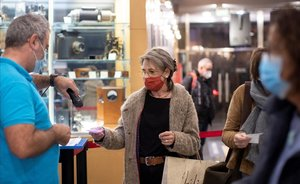 Una mujer con mascarilla valida su entrada en los cines Renoir de Barcelona.