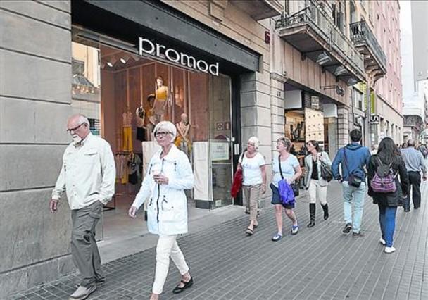 Unos transeúntes pasan ante comercios de la calle de Pelai.