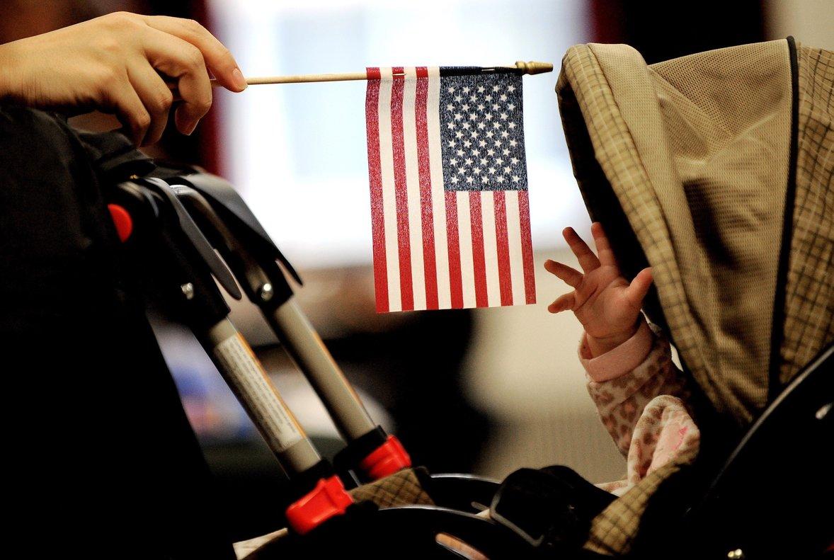 Un bebe intenta alcanzar la bandera estadounidense que sostiene su madre en Nueva York.