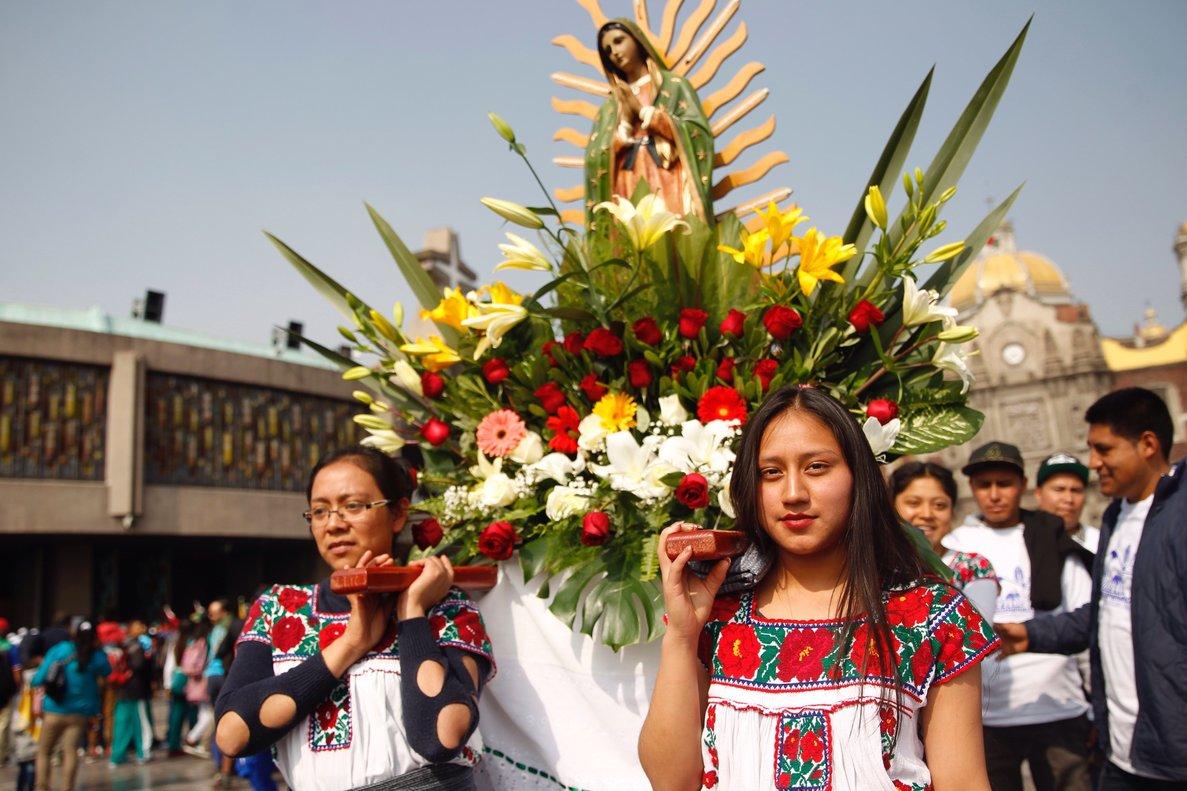 Dos jovenes cargan una corona de flores con la imagen de la virgen de Guadalupe luego de su llegada a las inmediaciones de la Basilica de Santa Maria de Guadalupeen Ciudad de Mexico.EFE Sashenka Gutierrez