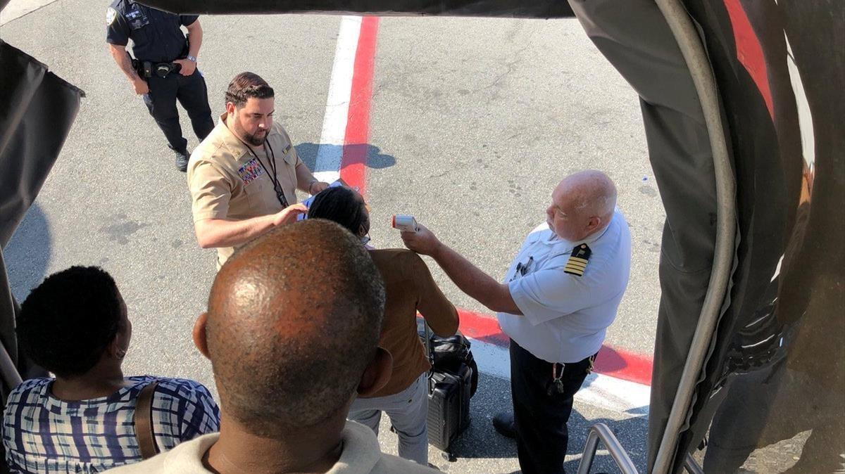 Pasajeros del vuelto de Emirates puesto en cuarentena siendo exhaminados en el aeropuerto de Nueva York