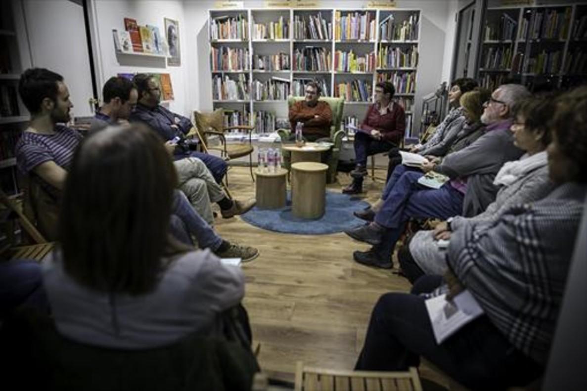 Jordi Puntí, en el sofà verde, habla con uno de los participantes en el club de lectura de Atzavara, en presencia de Susanna Àlvarez, sentada a su lado.