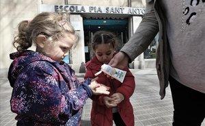 Dos niñas se aplican gel desinfectante al salir de la escuela, en Barcelona.