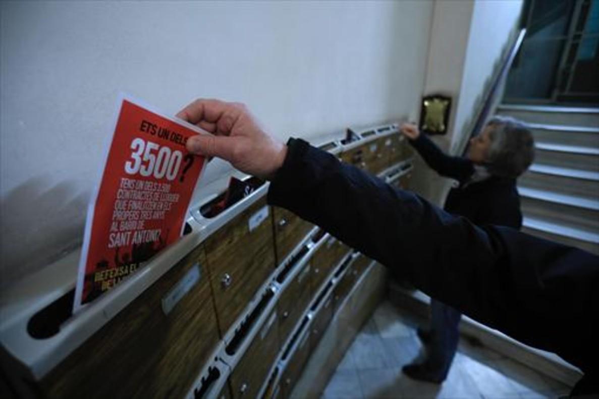 Elisa y Xavier depositan en los buzones de una finca de la calle de Rocafort folletos de la campaña contra el aumento exagerado de los alquileres de las viviendas del barrio.