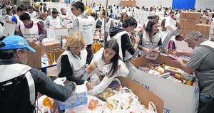 Un equipo de voluntarios clasifica los alimentos recolectados en un almacén de El Prat de Llobregat, el sábado.