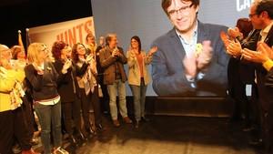 El escenario del mitin de JxCat en Girona, con Puigdemont en la pantalla y su esposa, aplaudiendo (en primera línea, la tercera por la izquierda).