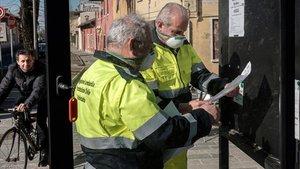 Funcionarios de Lombardía protegidos con máscaras colocan carteles en San Fiorano, una de las localidades en cuarentena en Italia, este lunes.