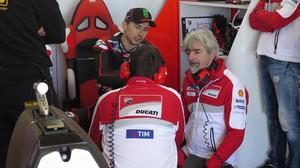 Gigi DallIgna, agachado, conversa con Jorge Lorenzo, en el box de Ducati.