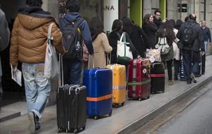 Procesión de turistas y maletaspor el centro de Barcelona.