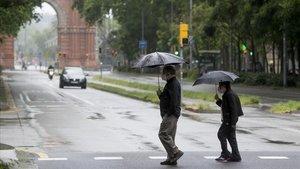 Dos transeúntes pasean bajo la lluvia frente al Arc de Triomf, el pasado domingo.