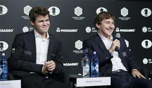 El noruego Carlsen (izquierda) sonríe mientras el derrotado ajedrecista ruso Karjakin habla en la rueda de prensa posterior a la partida definitiva.