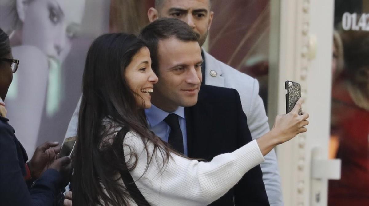 Macron se hace un selfie con una chica trascortarse el pelo este martes en una barbería de París.