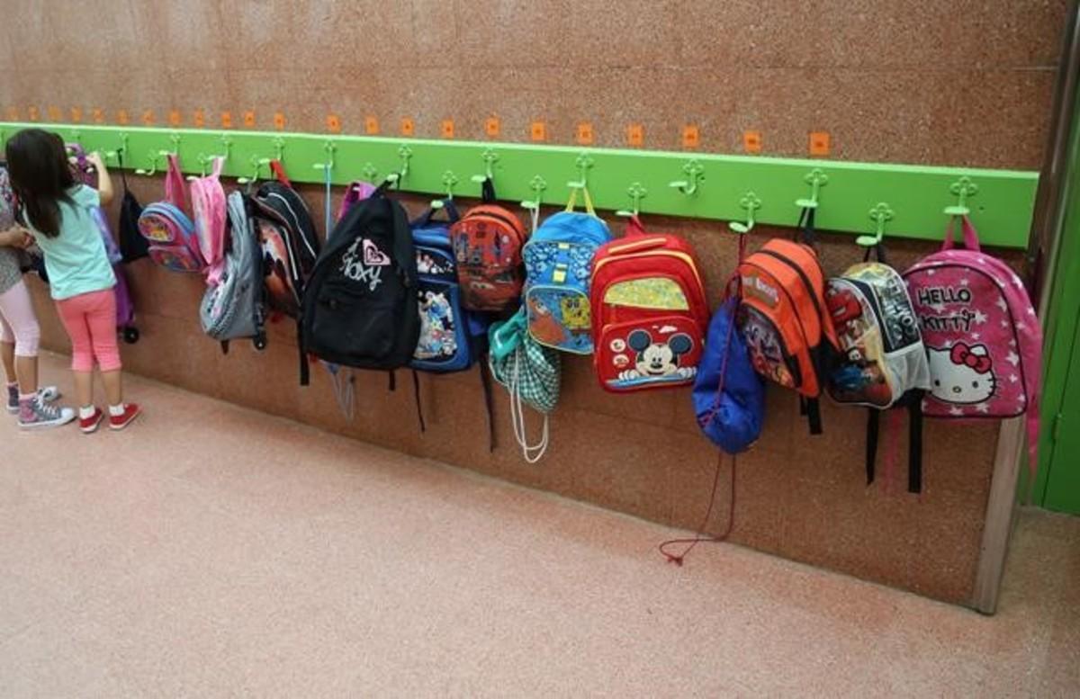 Una niña coloca su mochila en los colgadores de su clase de infantil en un colegio de Badalona.