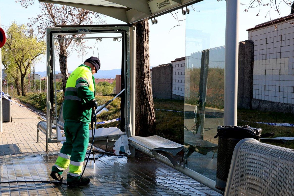 Un operario limpia la parada de autobús en la que un vehículo ha chocado en Sabadell.