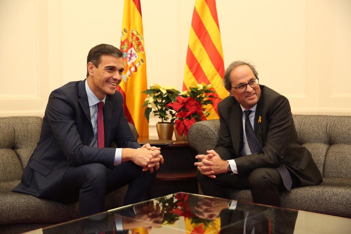 Pedro Sánchez y Quim Torra, con la flor de Pascua roja, delante de las dos amarillas.