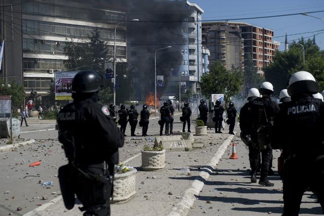 Policías antidisturbios intentan dispersar a un nutrido grupo de manifestantes en Mitrovica, este domingo.