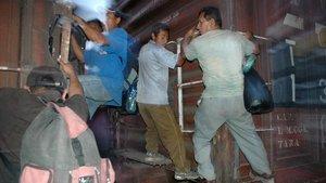 Inmigrantes viajan colgados en los vagones de un tren en su intento por asentarse en Estados Unidos.